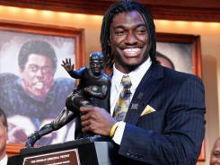 Baylor quarterback Robert Griffin III poses with the Heisman Trophy after becoming the 77th recipient of the award Saturday in New York City.