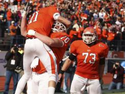 Sam Houston State's Brian Bell (11) celebrates with teammates Dan Jenkins (40) and Travis Watson (73) after scoring a touchdown against Montana State in Saturday's quarterfinal game.