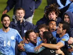 North Carolina players celebrate after defeating UCLA in penalty kicks. The Tar Heels take on Charlotte in the College Cup final on Sunday.