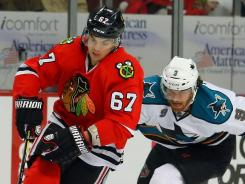 Chicago Blackhawks right wing Michael Frolik (67) is chased by San Jose Sharks right wing Martin Havlat (9) during the second period at the United Center in Chicago.