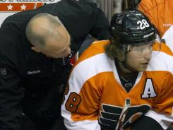 Philadelphia Flyers center Claude Giroux gets looked over by the training staff after getting hit in the head. He later left the game.