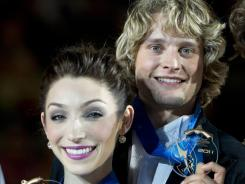 Ice dance gold medalists Meryl Davis and Charlie White hold up their medals during victory ceremonies at the ISU Grand Prix.