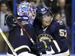 The Blues' David Perron, right, and goalie Brian Elliott celebrate the latter's shutout win against the Sharks on Saturday. Elliott is tied for the NHL lead in shutouts (four) with Los Angeles' Jonathan Quick.