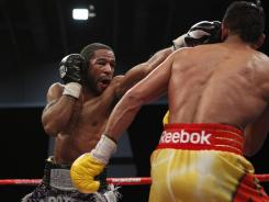 Lamont Peterson, left, connects against Amir Khan during their junior welterweight title fight Saturday night at the Convention Center in Washington, D.C. Peterson won the fight with a majority decision.