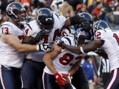 Offensive players mob teammate Kevin Walter after he caught the game-winning touchdown pass from rookie T.J. Yates with two seconds left to give the Texans the win and the first playoff berth in the franchise's history.