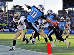 Tennessee Titans quarterback Jake Locker dives into the end zone for a touchdown against the New Orleans Saints.
