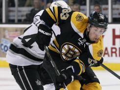 Brad Marchand (63) beats Justin Williams (14) to the puck in the second period of their game in Boston on Tuesday. Machand scored two goals in the Bruins' 3-0 win over the Kings.