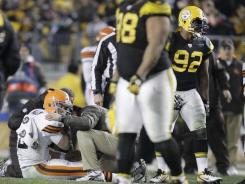 Trainers tend to Cleveland Browns quarterback Colt McCoy after he was hit by Pittsburgh Steelers outside linebacker James Harrison (92) during their game in Pittsburgh.
