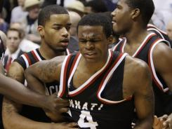 Cincinnati guard Ge'Lawn Guyn (14) is held back by Dion Dixon during a fight at the end of an NCAA college basketball game against Xavier, Saturday, Dec. 10, 2011, in Cincinnati. Xavier won 76-53.
