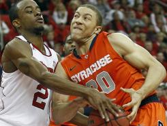 North Carolina State's Lorenzo Brown (2) fights with Syracuse's Brandon Triche for a rebound during the second half in Raleigh, N.C.