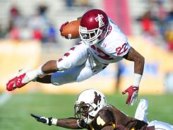 Temple Owls running back (22) Matt Brown leaps over Wyoming Cowboys safety (4) Tashaun Gipson in the second quarter of the New Mexico Bowl.