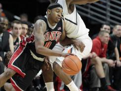 UNLV's Oscar Bellfield (0) slips past Illinois' D.J. Richardson (1)during the second half  in Chicago on Saturday.