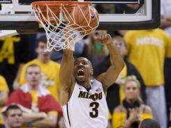 Missouri's Matt Pressey, top, dunks the ball in front of teammate Steve Moore (32) and William & Mary's Brandon Britt, left, during the first half of an NCAA college basketball game on Sunday, Dec. 18, 2011, in Columbia, Mo.