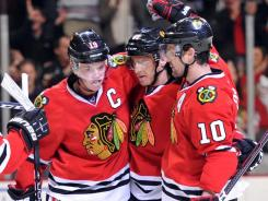 Blackhawks winger Marian Hossa, center, is congratulated by teammates after his third-period power-play goal.