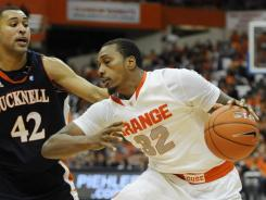 Syracuse forward Kris Joseph shakes off Bucknell guard Cameron Ayers during the first half at the Carrier Dome in Syracuse, N.Y.