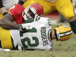 Packers quarterback Aaron Rodgers (12) is sacked by Chiefs defensive end Allen Bailey (97) as Kansas City ended Green Bay's perfect season, 19-14. Police say a drunken woman twice choked her 11-year-old daughter on Sunday after becoming angered by the game.