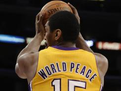 Laker forward Metta World Peace, formerly Ron Artest, gets a pass on the baseline in front of the Clippers' Chris Paul during an NBA preseason game at Staples Center.