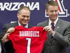 Rich Rodriguez, left, stands with Arizona athletics director Greg Byrne after being introduced as the new Wildcats coach.