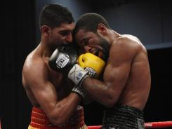 Amir Khan, left, and Lamont Peterson trade punches during their super lightweight world champion bout in Washington. Peterson won by split decision.