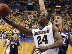 Missouri's Kim English (24) puts up a shot under pressure from Illinois' Meyers Leonard during the first half in St. Louis.