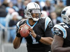 Cam Newton threw three TDs and ran for another as he broke the NFL rookie record for passing yards.