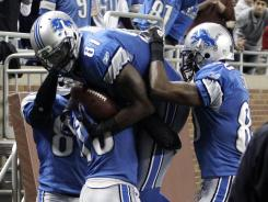 Lions WR Calvin Johnson (81) is mobbed by teammates after scoring a touchdown Saturday in Detroit's 38-10 win.