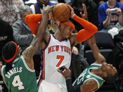 The Knicks' Carmelo Anthony, center, battles the Celtics' Marquis Daniels, left, and Rajon Rondo during New York's 106-104 win Sunday at Madison Square Garden.