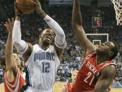 The first assignment for Samuel Dalembert, right, who signed with the Rockets on Monday, was trying to slow the Magic's Dwight Howard.