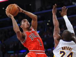 Reigning MVP Derrick Rose drives the lane vs. Lakers star Kobe Bryant during their matchup at the Staples Center. The Bulls' guard hit the go-ahead shot, finishing with 22 points.