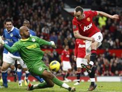 Manchester United's Dimitar Berbatov, right, scores past Wigan's goalkeeper Ali Al-Habsi during Monday's game. Berbatov recorded a hat trick in the 5-0 win.
