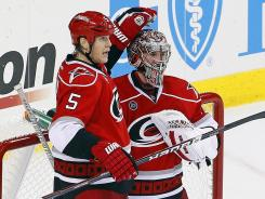 Hurricanes goalie Cam Ward is congratulated by Bryan Allen for his empty-net goal, the first time a goalie has scored in franchise history.