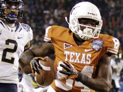 Texas wide receiver Marquise Goodwin (84) outruns California defensive back Marc Anthony (2) on a 47-yard touchdown pass during the third quarter of the Holiday Bowl in San Diego.