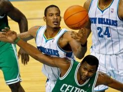 Hornets forward Trevor Ariza grabs a rebound over Boston Celtics guard Keyon Dooling during the fourth quarter at the New Orleans Arena.