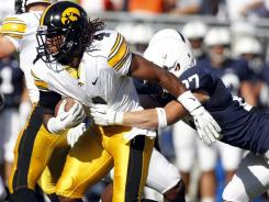 Jordan Bernstine of the Iowa Hawkeyes carries the ball on a kickoff return and is tackled by Jacob Fagnano of the Penn State Nittany Lions during the game on October 8, 2011 at Beaver Stadium in State College, Pennsylvania.