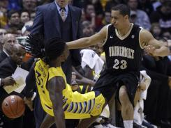 Marquette's Jae Crowder draws a charge from Vanderbilt's John Jenkins (23) during the first half in Milwaukee.