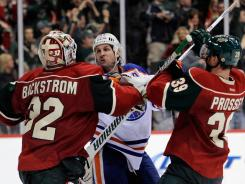The Oilers' Ryan Smyth, center, throws punches at goalie Niklas Backstrom (32) and Nate Prosser following a win by the Wild in St. Paul Minnesota. The game featured chippy play through out.