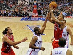 Bulls guard Derrick Rose puts up a shot as Clippers guard Chris Paul, center, defends and Bulls center Joakim Noah looks on during the first half of their game in Los Angeles. Rose had 29 points and 16 assists in Chicago's victory.