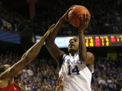 Kentucky forward Michael Kidd-Gilchrist shoots the ball against Louisville guard Chris Smith during the first half at Rupp Arena. Kidd-Gilchrist finished with 24 points and 19 rebounds.