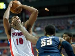 In a battle of former Georgetown Hoyas, Pistons forward Greg Monroe shoots over Pacers center Roy Hibbert during their game in Auburn Hills, Mich. Monroe, who finished with 19 points and 11 rebounds, helped Detroit past Indiana for its first win of the season.