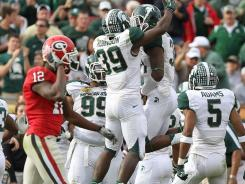 Michigan State cornerback Darqueze Dennard (31) is congratulated by teammates after an interception in the second half.