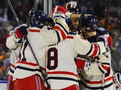 New York Rangers players celebrate after a goal by left wing Mike Rupp during the second period .