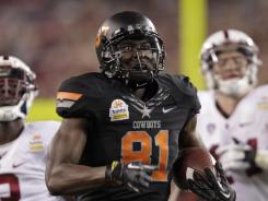 Held without a catch in the first quarter, Oklahoma State wide receiver Justin Blackmon races to the end zone for one of his three touchdowns. He finished with eight receptions for 186 yards.