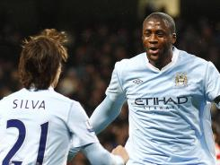 Manchester City's Yaya Toure, right, celebrates with teammate David Silva after scoring against Liverpool at The Etihad Stadium in Manchester.
