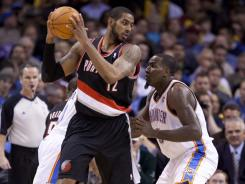 Trail Blazers forward LaMarcus Aldridge (12) goes to the basket against Thunder center Kendrick Perkins (5) in the first half. Aldridge led all scorers with 30 points as Portland surprised Oklahoma City.