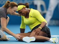 Serena Williams grimaces in pain while receiving treatment after injuring her left ankle during her match against Bojana Jovanovski. Williams won the match, but  she later withdrew from the event.