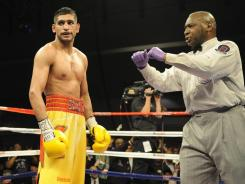 Amir Khan looks on after referee Joe Cooper took a point from him during his title fight loss to Lamont Peterson in Washington, D.C. in December.