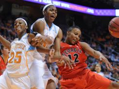 Tennessee's Glory Johnson (25) and  Vicki Baugh (21) battle Georgia's Jasmine Hassell for the ball during the game at Thompson Boling Arena in Knoxville.