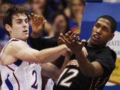 Kansas guard Conner Teahan battles for a rebound with Towson forward Erique Gumbs during the first half of an NCAA college basketball game in Lawrence, Kan., Friday, Nov. 11, 2011.