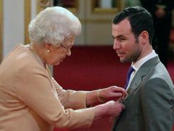 British cyclist and world road race champion Mark Cavendish, here being made an MBE by Britain's Queen Elizabeth II at Buckingham Palace in November, says an administrative error caused him to miss a drug test.
