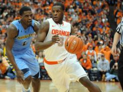Syracuse Orange guard Dion Waiters dribbles past Marquette Golden Eagles guard Darius Johnson-Odom during the second half of a game at the Carrier Dome. Syracuse won the game 73-66.